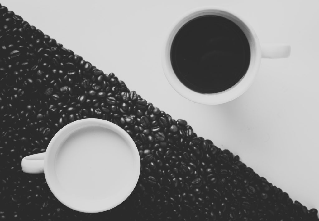 Yin Yang arrangement with two white coffee cups filled with black coffee and milk. Photograph by Alex.