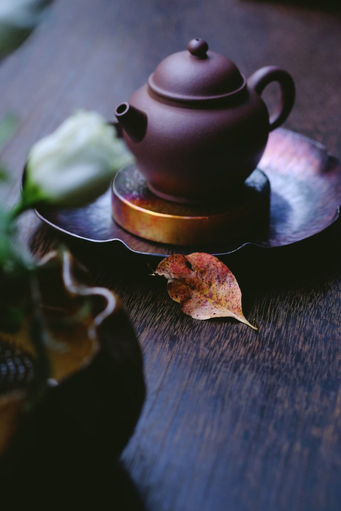 Earthen pottery teapot with leaves. Photograph by Oriento
