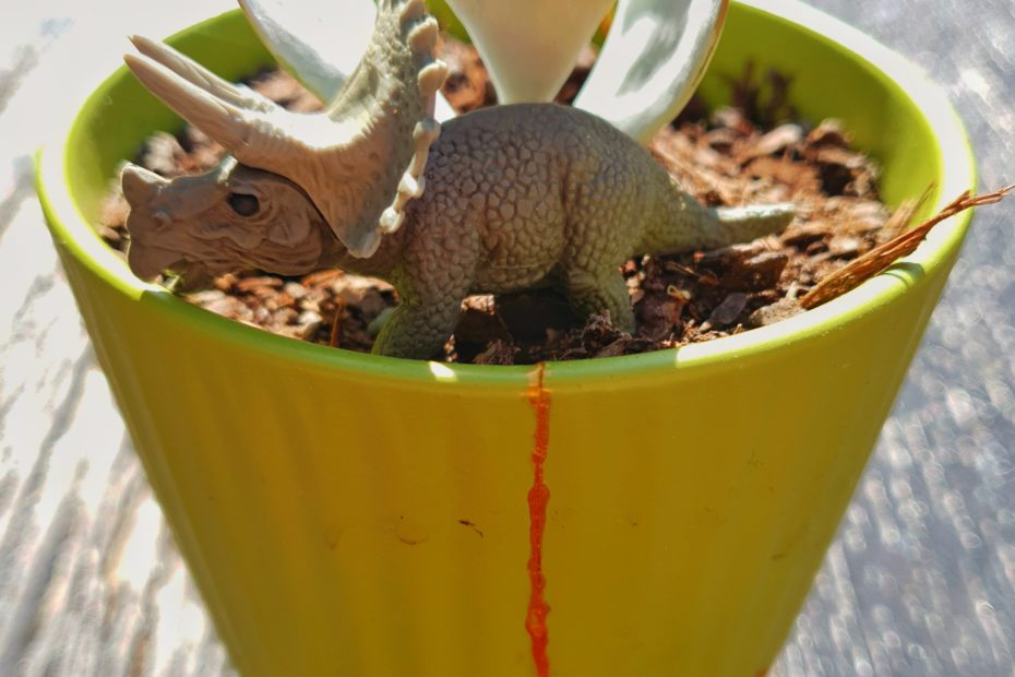 Green pot with kintsugi gold cracks. Small potted plant and small toy triceratops. Mixed medium art by AdeleAria