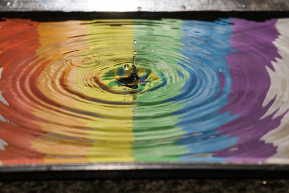 rainbow reflected in a pool of water with a splash. Photograph by Jordan McDonald