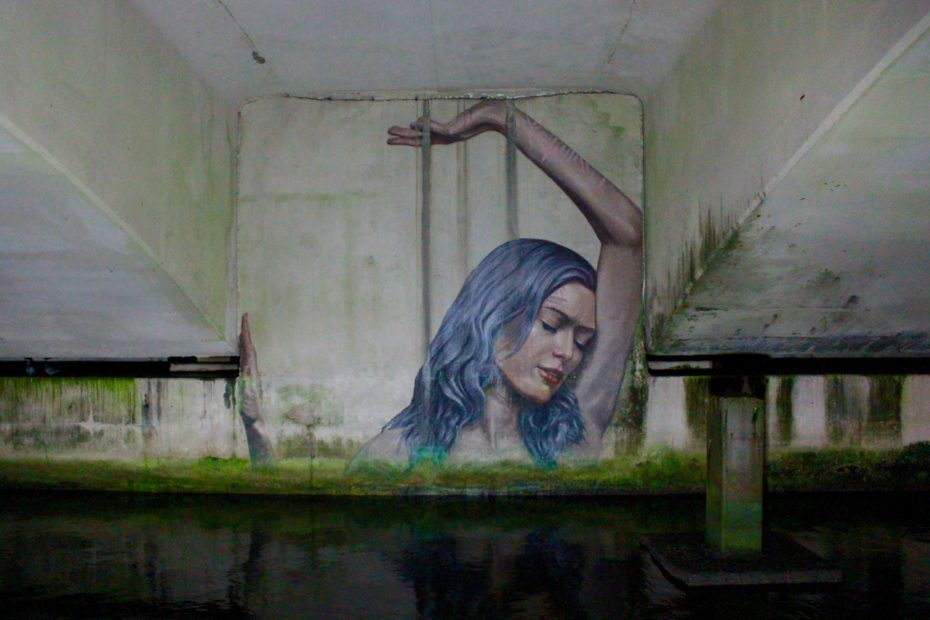 Graffiti art of blue haired woman pushing against concrete walls. Photograph by Joe Pregadio