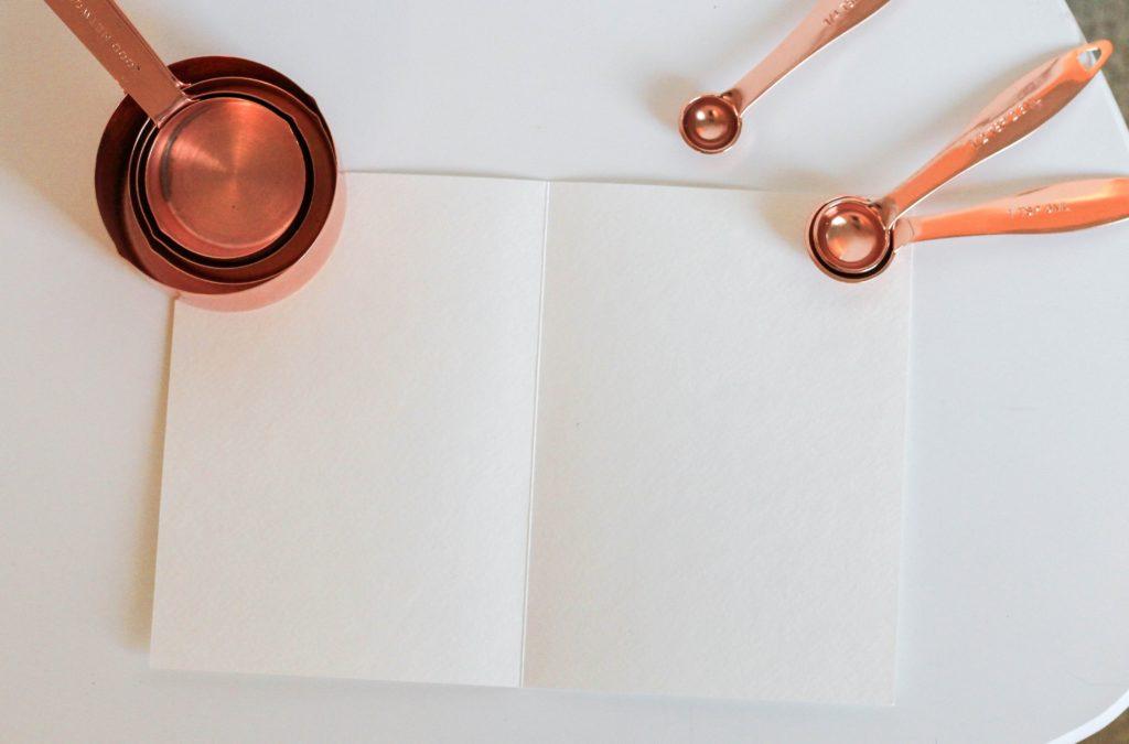 Brass measuring instruments around a blank recipe book. Image by Kara Eads.