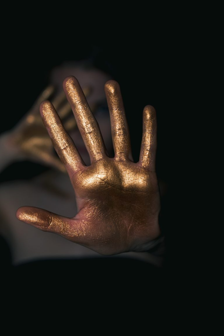 Gold hand in foreground before covered face. Image by Laura Dewilde