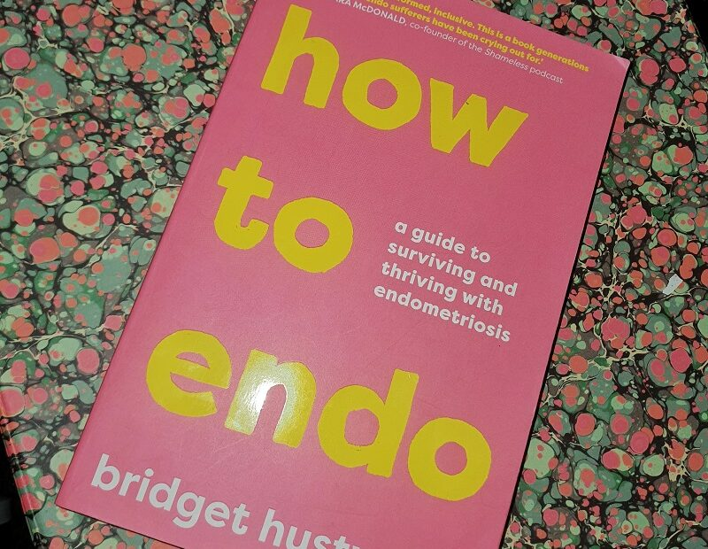 "Book ""how to endo"" with a pink cover and yellow and white text, sitting on a background of multi-coloured bubbles"